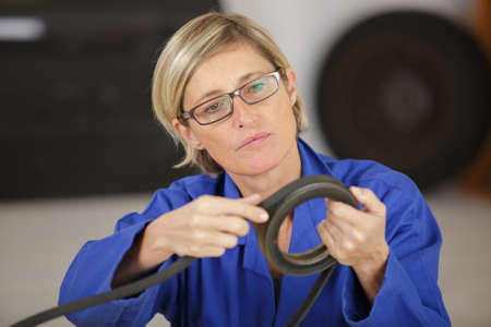 female mechanic with a distribution belt in her hands