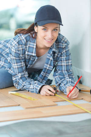 craftmanship: craftswoman measuring wooden plank with ruler and pencil Stock Photo
