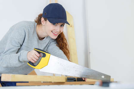 happy girl is sawing a wooden beam Stock Photo