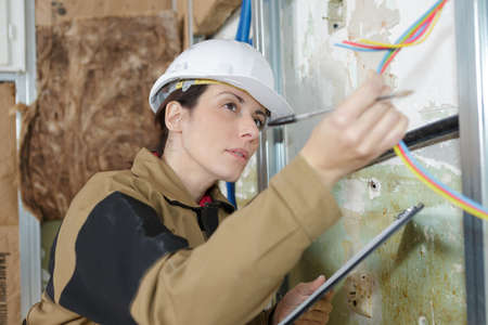 female electrician inspecting the cables Stock Photo