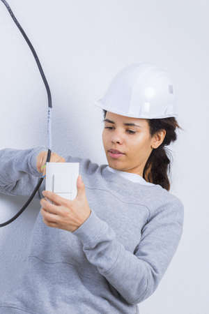 woman fitting an electrical outlet in bathroom