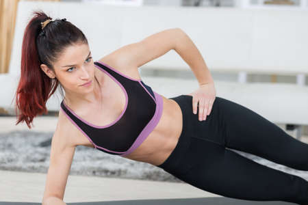 woman while doing side plank on a mat Stock Photo