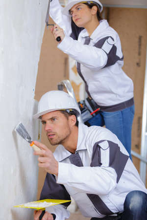 sidewall: male and female plasterer in uniform polishing the wall Stock Photo