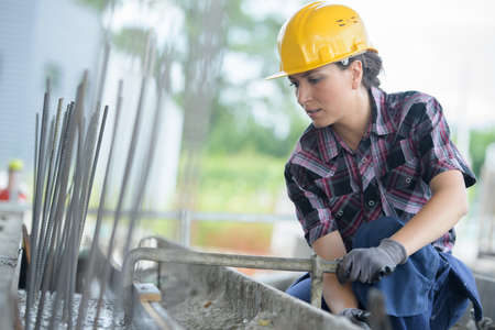 tiredness: woman working on metal structure Stock Photo
