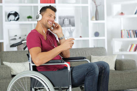 man happy in a wheelchair listening to music