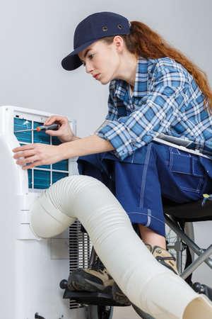 エアコンのメンテナンスをしている女性
