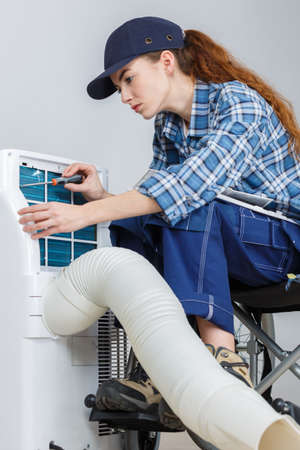 woman doing the maintenance of air-conditioning