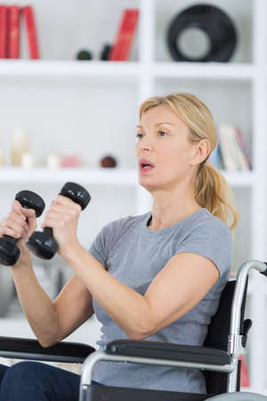 patient lifting dumbbell in clinic Stock Photo