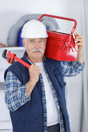 senior builder holding a red tool box Stock Photo