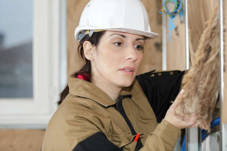 female construction worker installing insulation Stock Photo