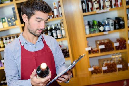 salesman taking inventory in wine shop Stock Photo