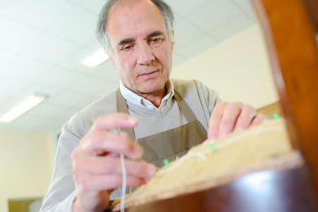 artisan designer finishing off the sanding in his studio