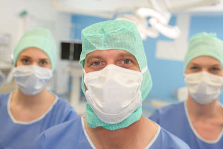 three surgeons at work operating in surgical theatre