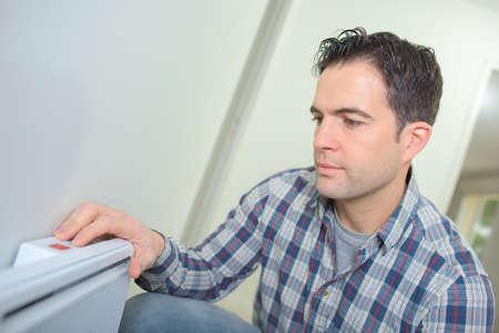 man changing temperature of radiator