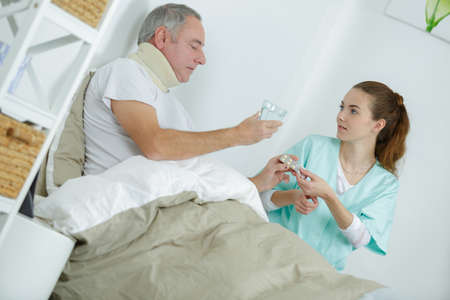 caring nurse helping sick man to drink in bed