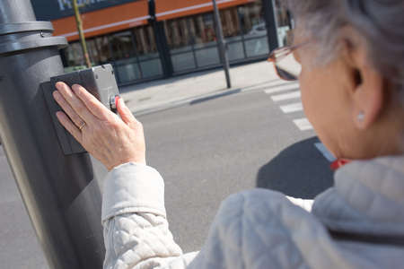 pause button: old lady pressing button at traffic lights on pedestrian crossing Stock Photo