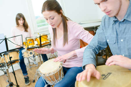 youg girl learning to play the drums Stock Photo