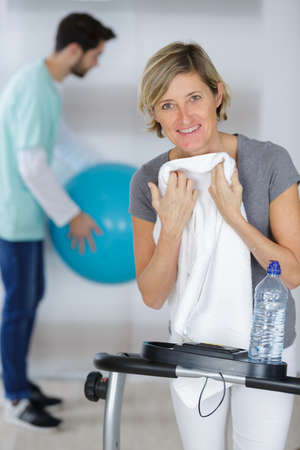 woman after exercising with her experienced young physiotherapist