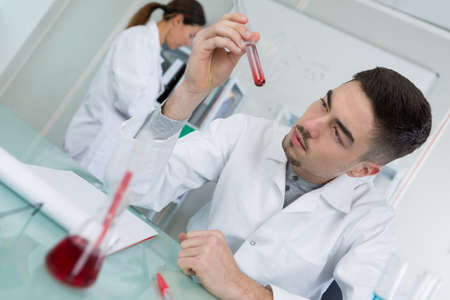 male scientist holding test tube with blood sample Stock Photo