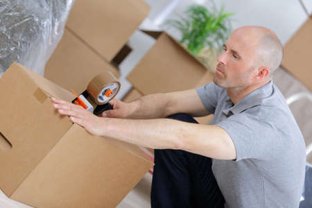 moving box: man is packing and using an adhesive tape Stock Photo