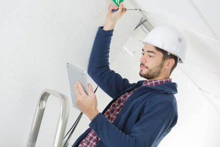 builder checking on tablet how to fix ceiling Stock Photo
