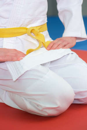boy stands in white kimono with a yellow belt Stock Photo