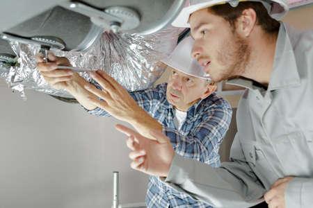 werknemers die ventilatiepijpen bevestigen