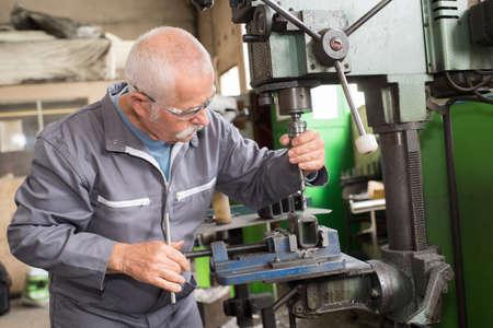 高齢労働者の時計フライス盤の詳細の処理 写真素材