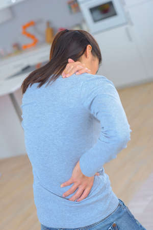 attractive woman with back pain at home Stock Photo