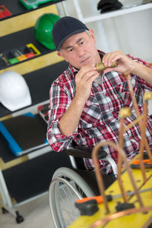 manual worker in wheelchair working with pipes
