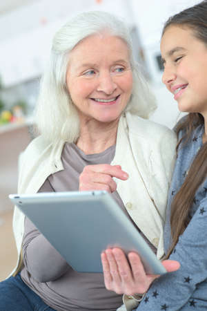 the grand daughter: girl teaching grandmother how to use a tablet