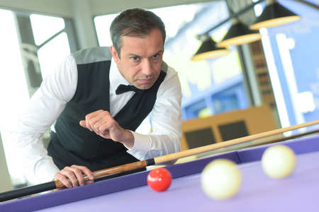 man playing pool in a bar Stock Photo