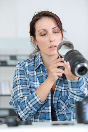 female photographer looking at zoom lens