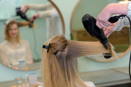 hate: professional hairdresser drying hair Stock Photo