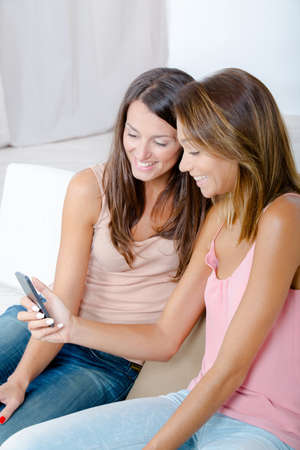 complicity: Women on sofa laughing at cellphone image