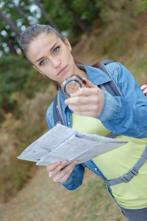young woman searching direction with a compass Banco de Imagens