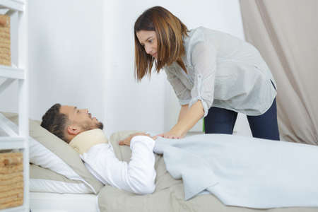 girlfriend takes care of man sick in the on bed Stock Photo