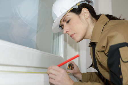 woman window setter marking the measurements Stock Photo
