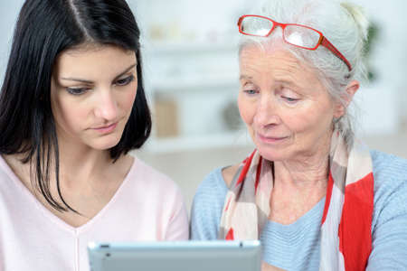sad elderly woman and relative with tablet