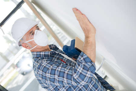 man stroking plaster to give it a finished look Stock Photo