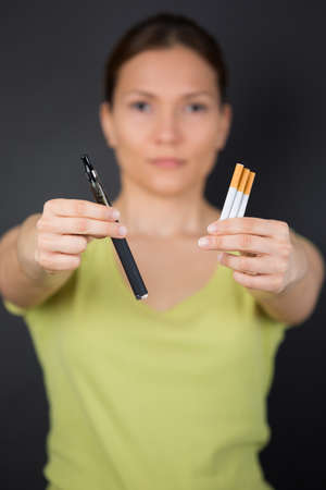 female choosing e-cigarette or tobacco cigarette Stock Photo