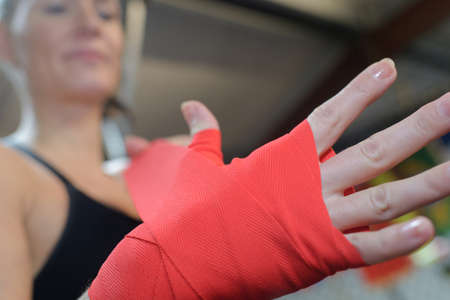 woman is wrapping hands with red boxing hand wraps