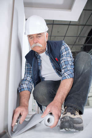 builder placing paper on the wall Stock Photo