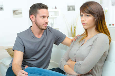 picture of young sad couple quarreling while sitting on sofa