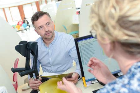 fysiotherapeuten secretaris bespreken met patiënt in de kliniek Stockfoto