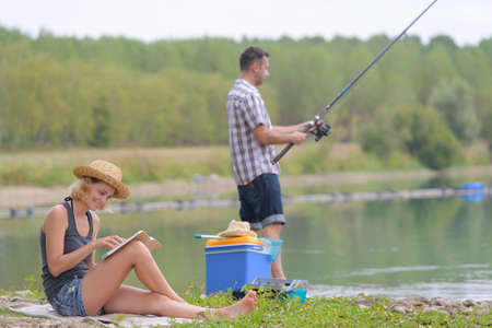young couple fishing on the banks of the pond Stock Photo