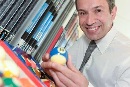 handsome businessman holding billiard ball