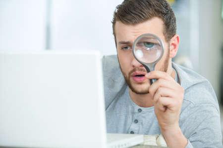 eman kijkt door vergrootglas Stockfoto