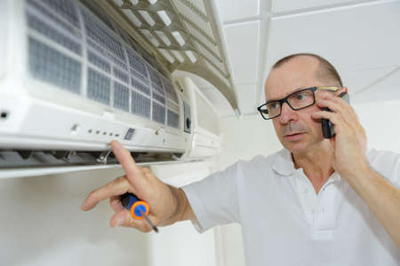phon: air-conditioning technician talking on mobile phon Stock Photo