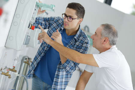 electrician and supervisor measuring voltage in fuse board